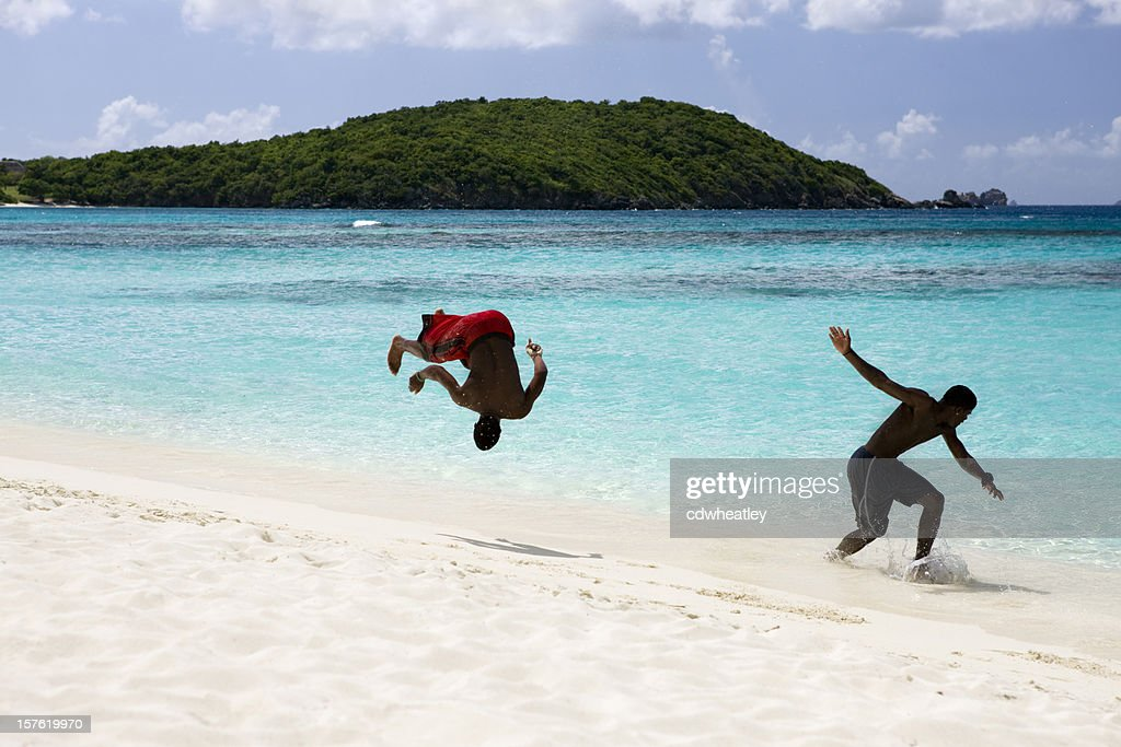 4128f97914307c teenagers doing back-flips at the beach shoreline   Stock Photo