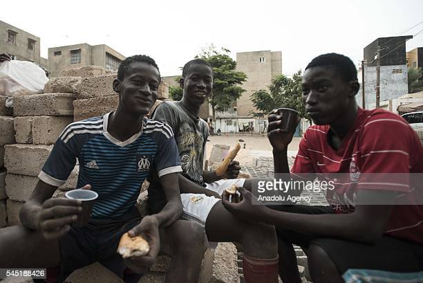 Teenagers eat and drink during the last day of Ramadan ahead of Eid day at HLM Market on July 05 2016 in Dakar Senegal