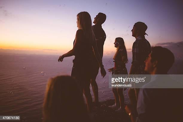 Adolescentes a desfrutar de um pôr do sol sobre uma montanha