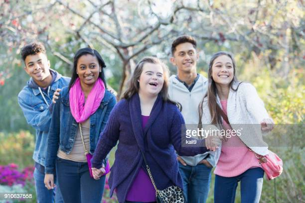 teenagers exploring a park, with down syndrome girl - developmental disability stock photos and pictures