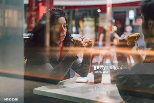 teenager-freunde sitzen gemeinsam beim fast food - schnellimbiss stock-fotos und bilder