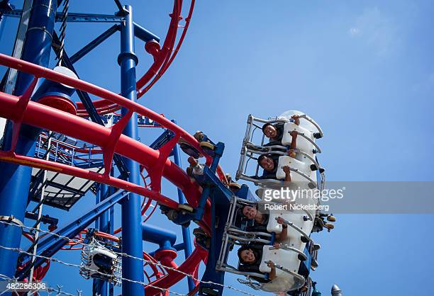 Teenagers gaze out while strapped into the Soaring Eagle amusement park ride July 24 2015 at Coney Island Beach in the Brooklyn borough of New York