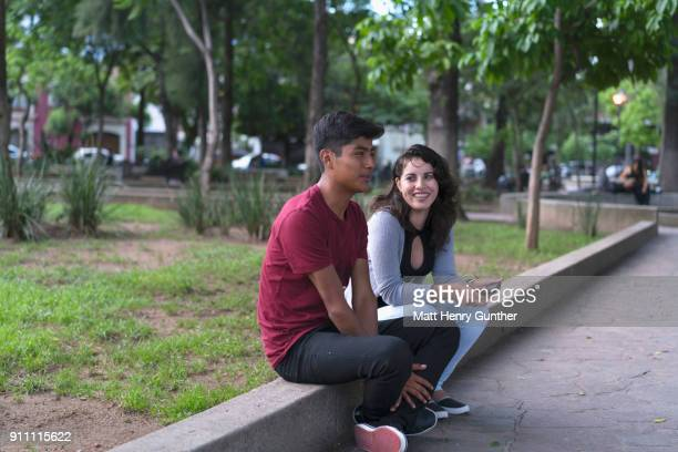 teenagers hanging out on street curb smiling and talking - henry street stock pictures, royalty-free photos & images
