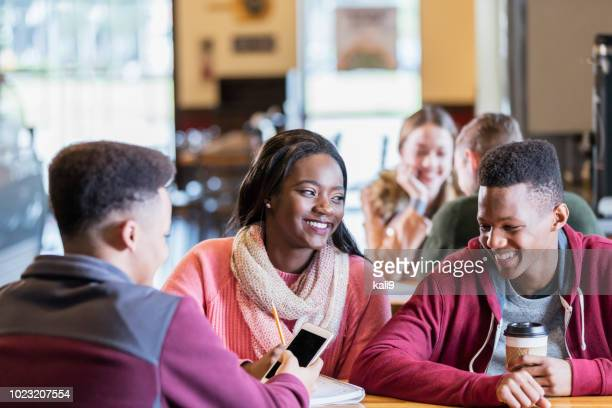 teenagers hanging out together in coffee shop - teenagers only stock pictures, royalty-free photos & images