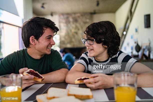 tieners die ontbijt hebben - broer stockfoto's en -beelden
