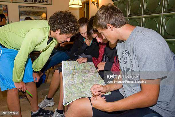 Teenagers Holding Map Indoors, Sonthofen, Schattwald, Bavaria, Germany