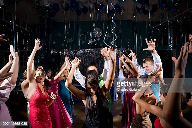 teenagers (15-18) in formalwear dancing at prom, arms raised - prom stock pictures, royalty-free photos & images
