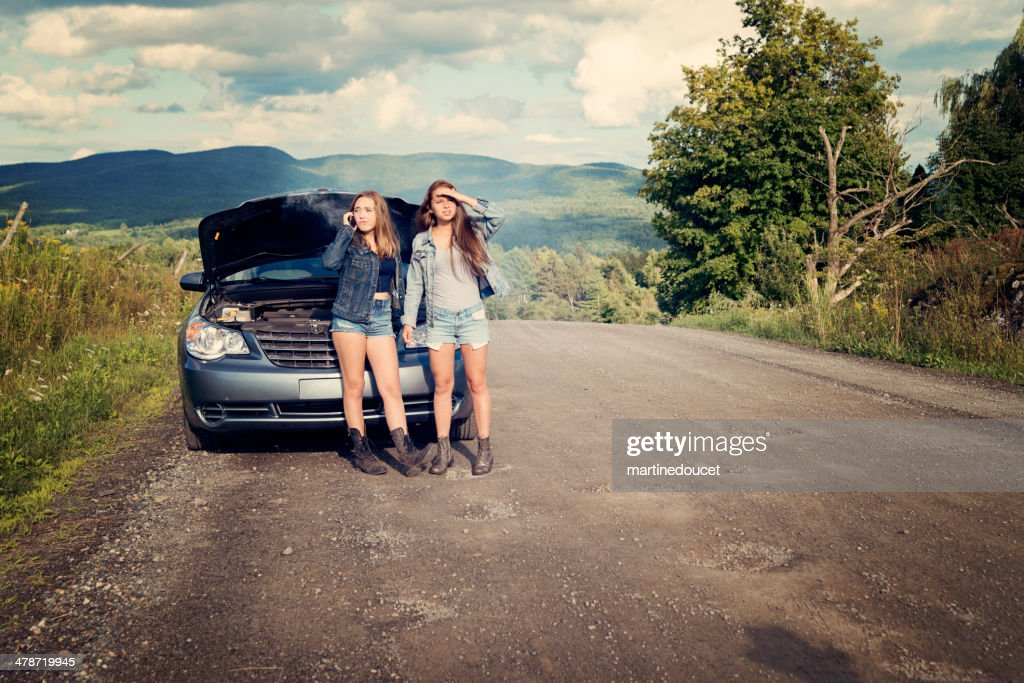 Teenagers in trouble on road with brokedown parent's car. : Stock Photo
