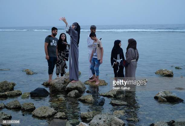Teenagers including girls wearing abayas that break markedly from the traditional black shoot selfies as they step among stones in the water of the...