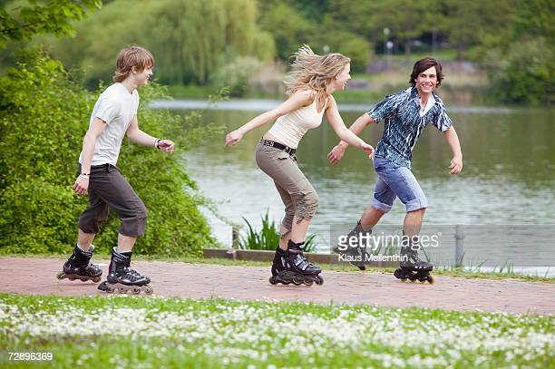 Teenagers inline skating, smiling