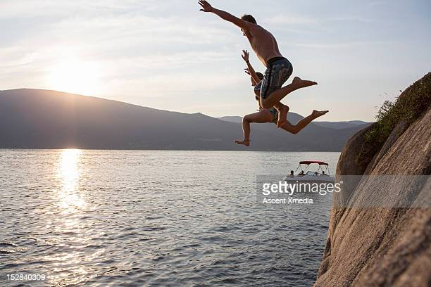 Teenagers jump form cliff into lake, boat below