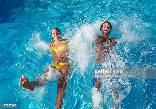 Teenagers jumping into swimming pool