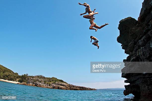 teenagers jumping off low cliff into water - david cliff stock pictures, royalty-free photos & images