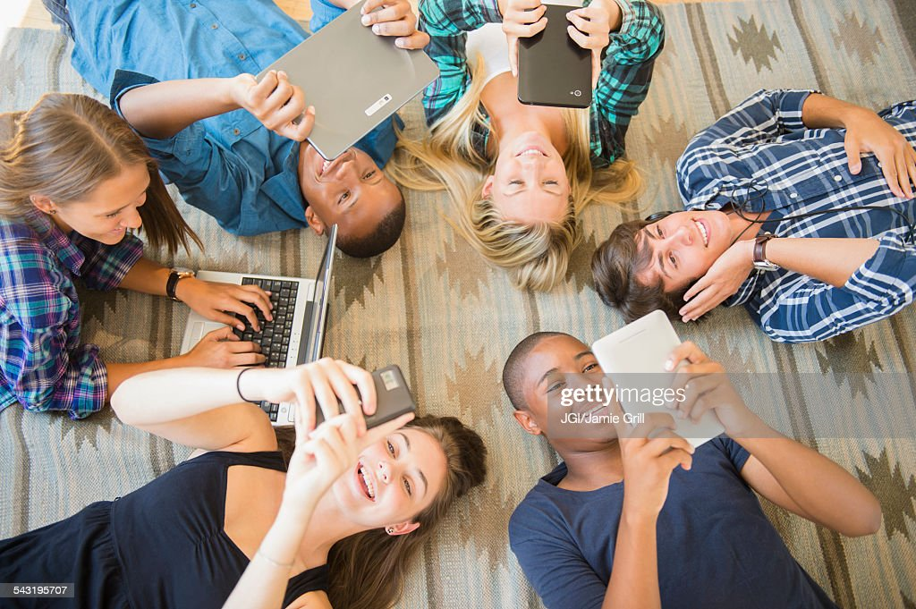 Teenagers laying on floor using technology : Stock Photo