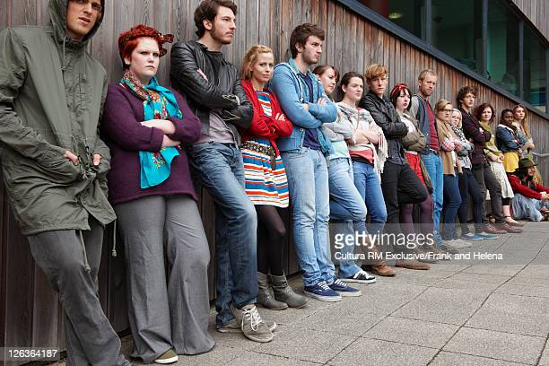 teenagers lined up against wall - newpremiumuk stock pictures, royalty-free photos & images