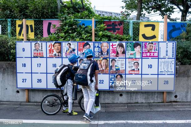 Teenagers looking at an election board with different candidates posters. Tokyo holding Gubernatorial Election 2020 today, Tokyo residents will vote...