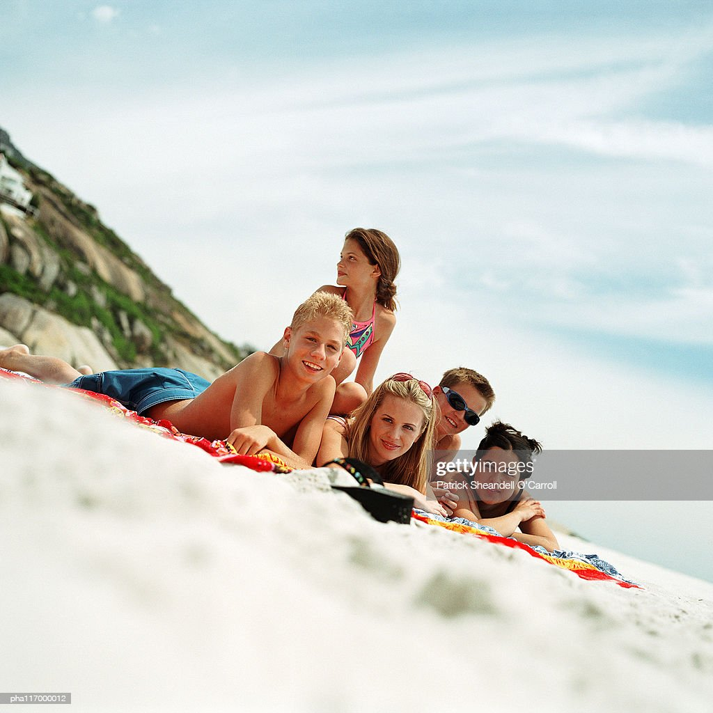 Teenagers lying on beach towels at the seashore : Stockfoto