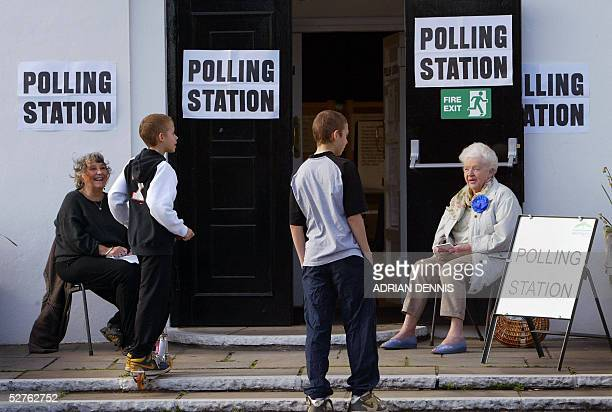 Teenagers make a request to vote at a polling station in Stanwell Village west of London 05 May 2005 The two ladies Labour and Conservative Party...