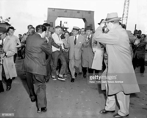 Teenagers mob Frank Costello as he leaves Rikers Island ferry after his release from the pen Morris Shilensky one of his lawyers is on the right