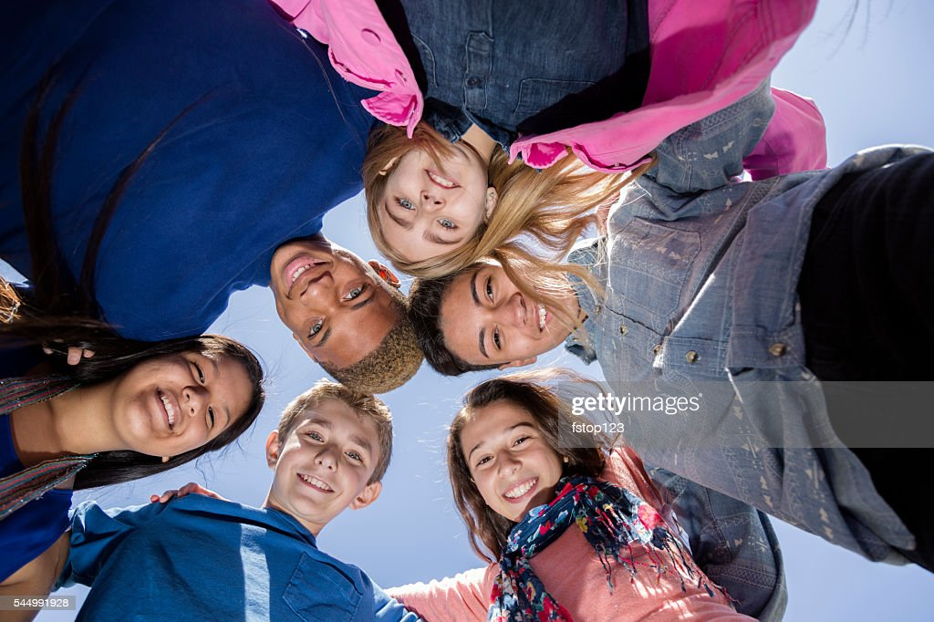 Teenagers: Multi-ethnic group of friends huddle outside together. Blue sky. : Stock Photo