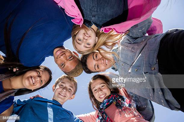 Teenagers: Multi-ethnic group of friends huddle outside together. Blue sky.