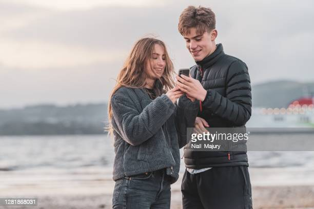 teenagers on a beach looking at a mobile phone - ireland stock pictures, royalty-free photos & images