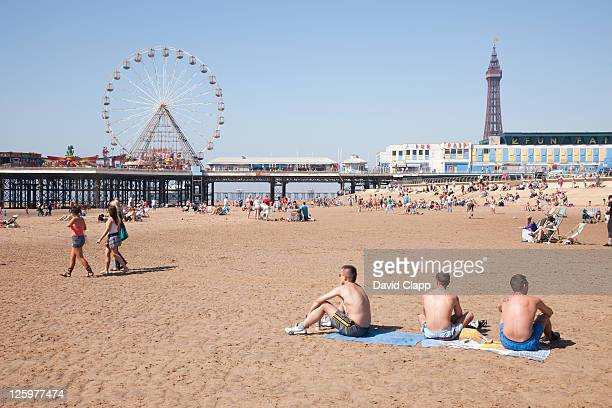 Teenagers (16-17 years old) on beach near Central Pier and Blackpool Tower on Blackpool Beach, Blackpool, Lancashire, England, UK