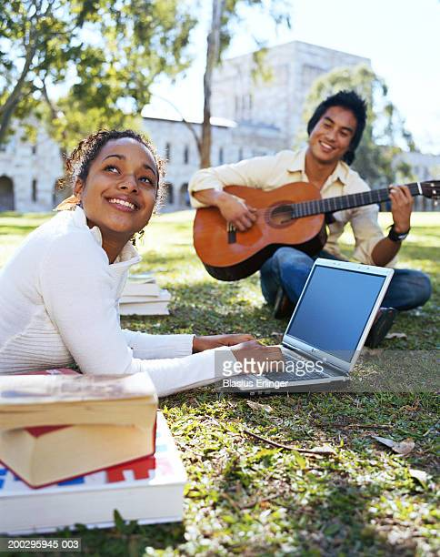 teenagers (16-20) on campus lawn playing guitar and using laptop - blasius erlinger stock pictures, royalty-free photos & images