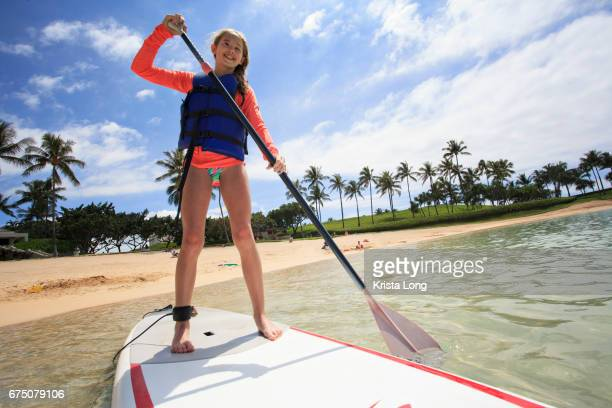 Teenagers paddle boarding in Hawaii on vacation.