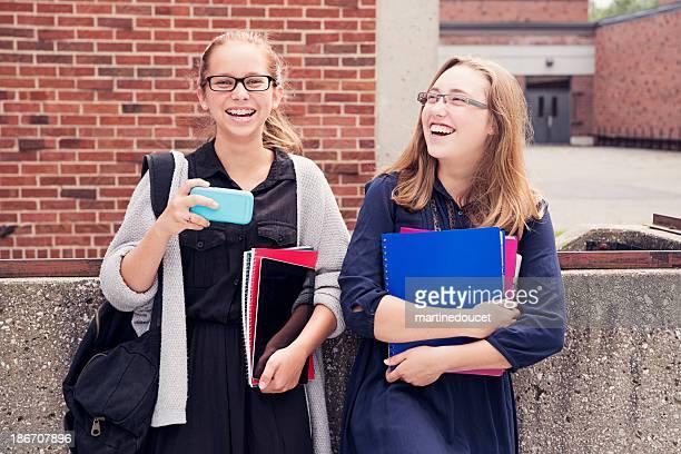 """adolescentes fotografiar por teléfono móvil en la parte delantera de la escuela secundaria. - """"martine doucet"""" or martinedoucet fotografías e imágenes de stock"""