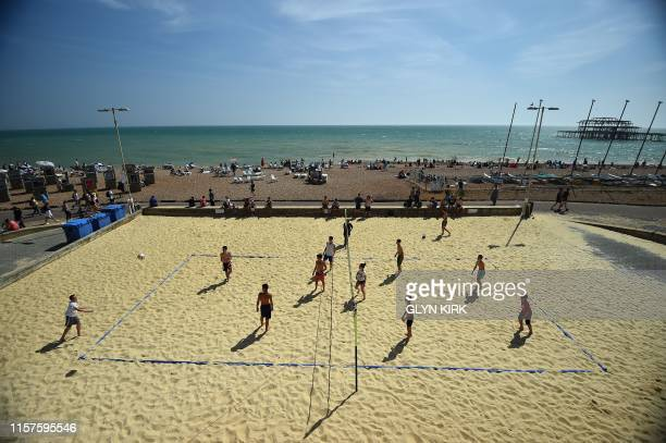 TOPSHOT Teenagers play volleyball by the sea in Brighton southern England on July 24 2019 during a heatwave in Britain Temperatures soared above 30C...