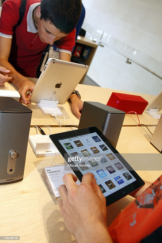 Teenagers play with iPads as they attend the opening of Apple's New Barcelona Store in Passeig de Gracia on July 28, 2012 in Barcelona, Spain.