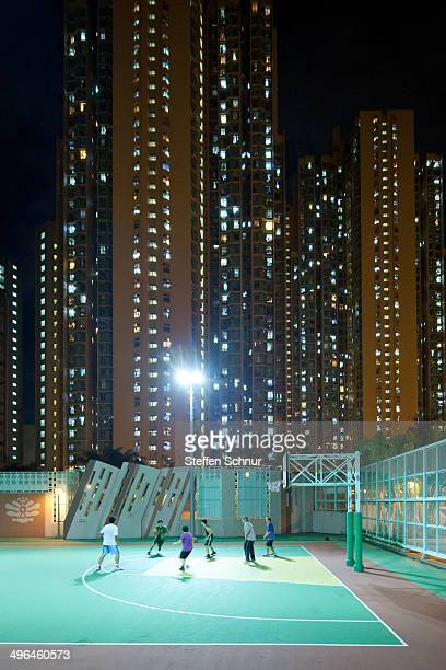 Teenagers playing basketball in front of the mighty skyscraper facades in Hong Kong
