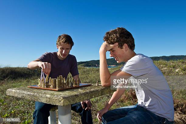 Teenagers playing chess at beach