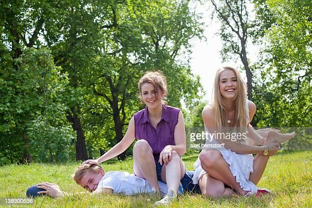 teenagers playing in grass in park - dominanz stock-fotos und bilder