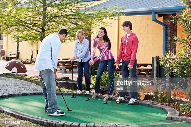 Teenagers playing miniature golf