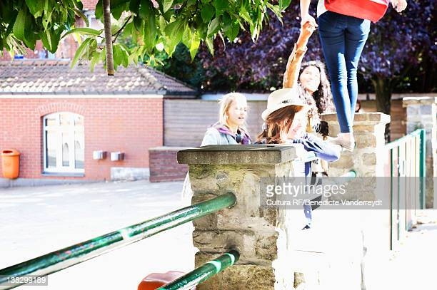 Teenagers playing on school wall