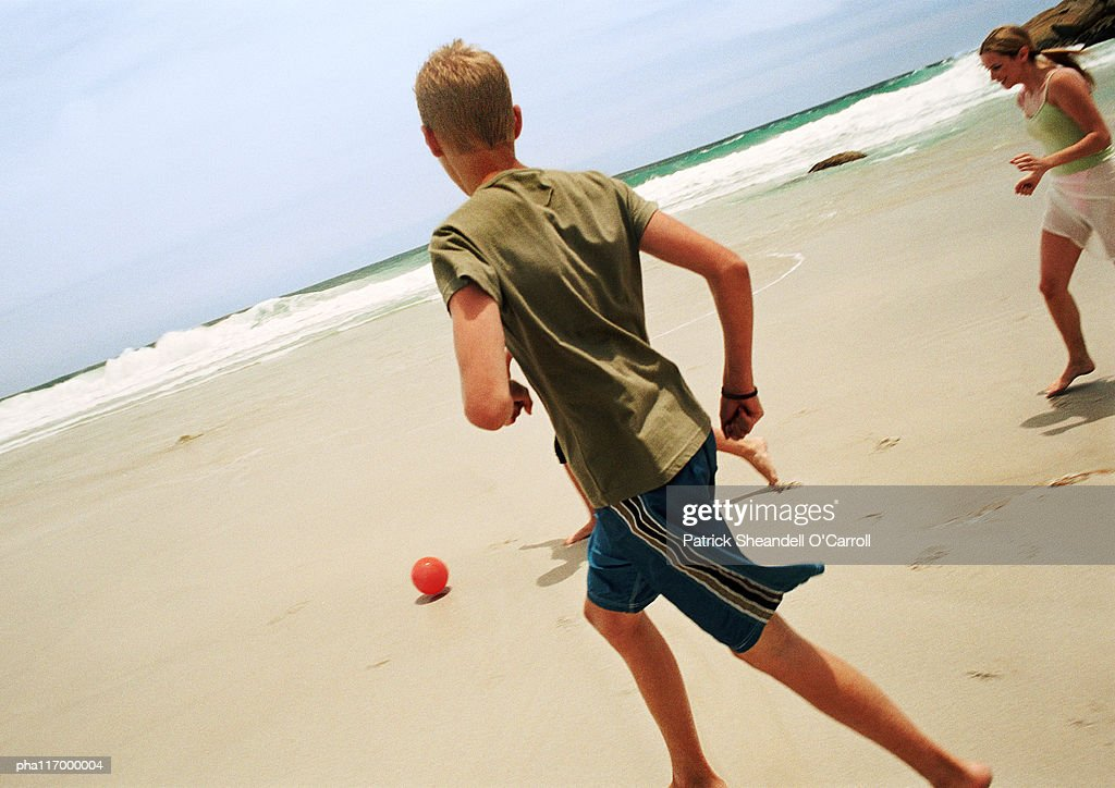 Teenagers playing soccer at the beach : ストックフォト