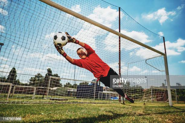 teenagers playing soccer - scoring a goal stock pictures, royalty-free photos & images