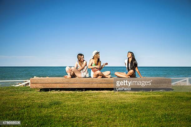 Teenagers playing ukulele and singing in front of the beach