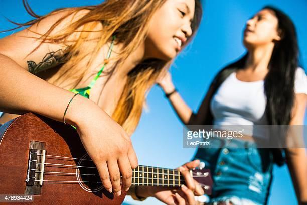 teenager spielen wie man ukulele spielt und singt vor dem strand - ukulele stock-fotos und bilder