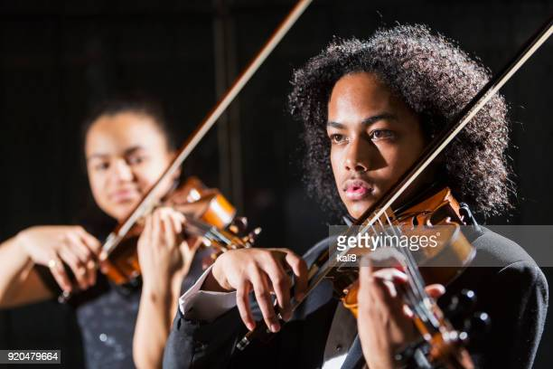 Teenagers playing violins in concert, focus on boy