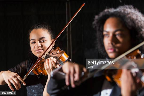teenagers playing violins in concert, focus on girl - child prodigy stock pictures, royalty-free photos & images