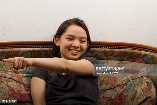 teenager's portrait sat on a sofa - jean marc payet stockfoto's en -beelden