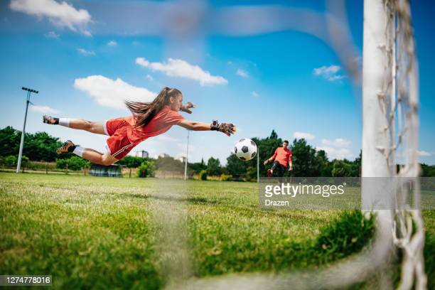 teenagers practicing penalty kicks and playing soccer. female goalkeeper playing football with friend - penalty kick stock pictures, royalty-free photos & images