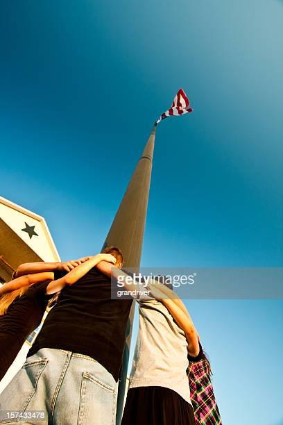 Adolescents prier autour d'un mât du drapeau