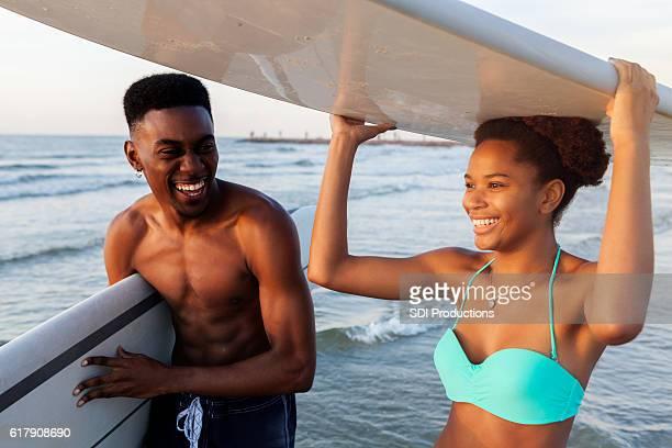 Teenagers prepare to surf in the ocean