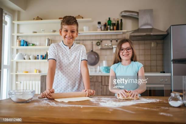 adolescents préparant des biscuits - plan moyen angle de prise de vue photos et images de collection
