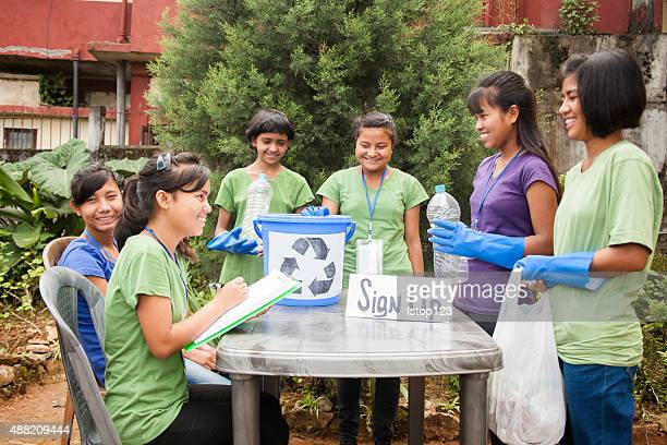 teenagers register at recycling volunteer check-in table. multi-ethnic group. - charity and relief work stock pictures, royalty-free photos & images