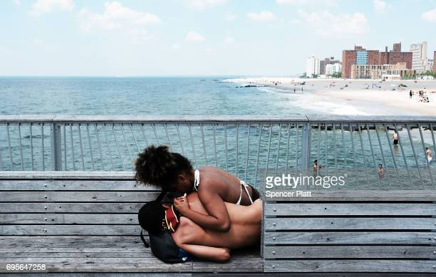 Teenagers relax along the boardwalk on a hot day at Coney Island on June 13 2017 in the Brooklyn borough of New York City Despite a mostly wet and...